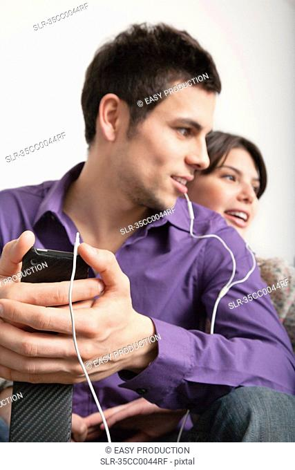 Smiling couple listening to headphones