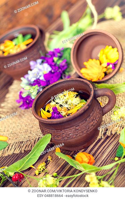 Two ceramic cups of healthy herbal tea with decoction of dry and fresh flowers on dark aged rustic wooden background. Shallow depth of field