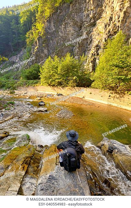 young man with backpack enjoying on mountain and waterfall