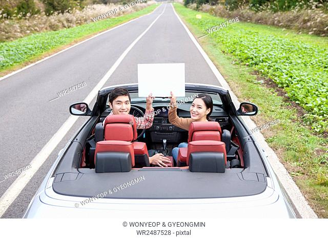 Young smiling couple in a car holding a paper looking back