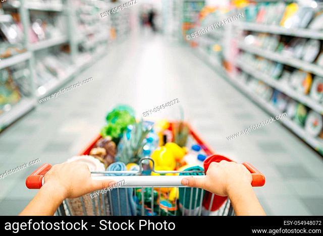 Female person hands drags the cart full of goods in a supermarket, shopping. Customer in shop, buyer in market, shopping concept