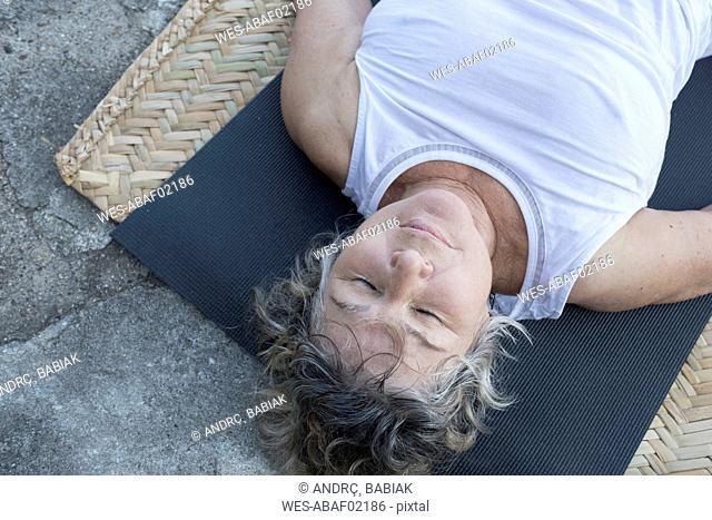 Senior woman lying on yoga mat with closed eyes