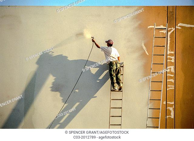 Balancing on a ladder, a Hispanic workman spray paints a factory wall in Irvine, CA. Note long shadows from afternoon sun