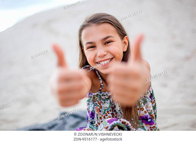 little girl showing thumbs up with both hands
