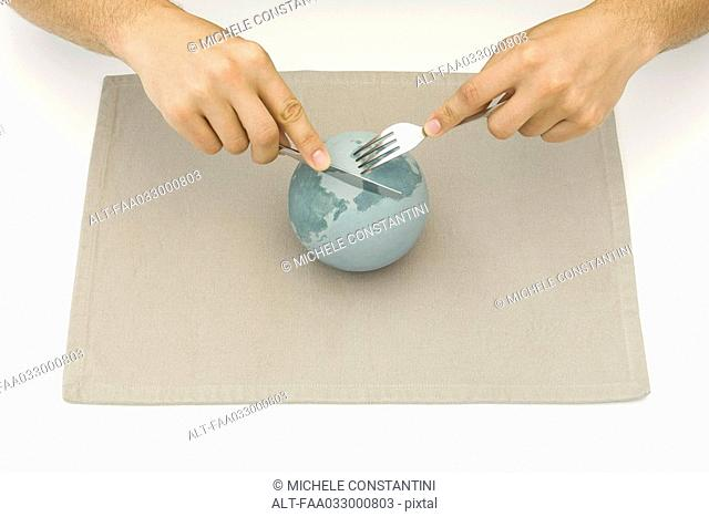 Globe resting on placemat, hands using knife and fork to cut up globe
