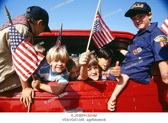 Cub Scouts waving American flags from back of car, Los Angeles, California