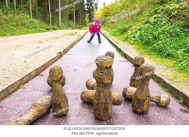 Young girl plays at skittles on a forest playground