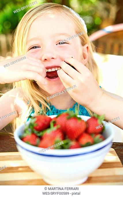 Portrait of happy girl eating stawberries