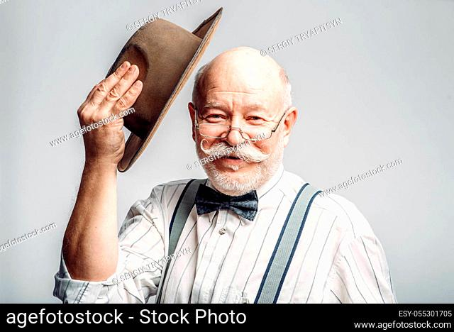Elderly man in a bow tie and glasses takes off his hat, grey background. Mature senior looking at camera in studio