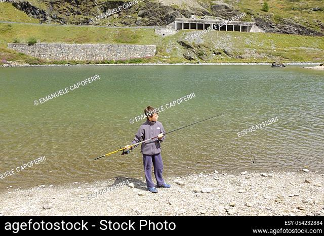 Boy fishing in the lake Foscagno, Lombardy, Italy
