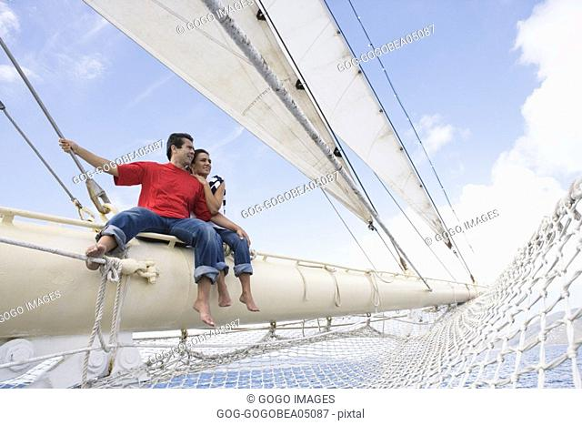Couple sitting on ship rigging