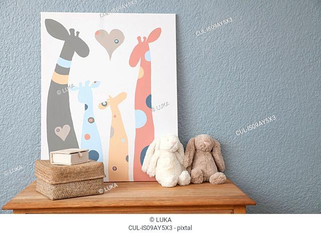 Picture and soft toys on chest of drawers in baby's nursery