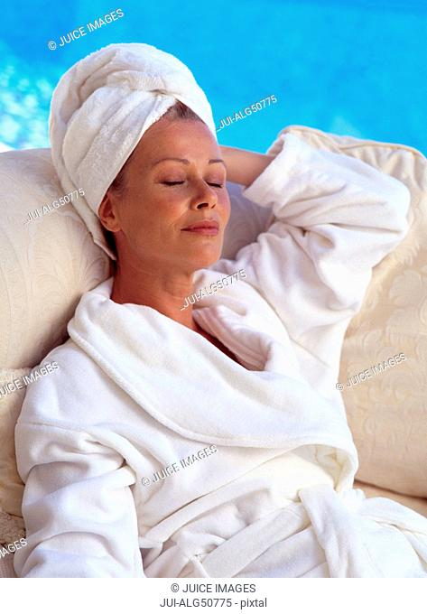 Woman relaxing beside pool at spa