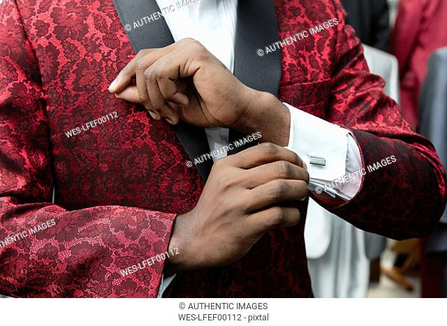 Close-up of a man wearing tuxedo in tailor shop adjusting the sleeves
