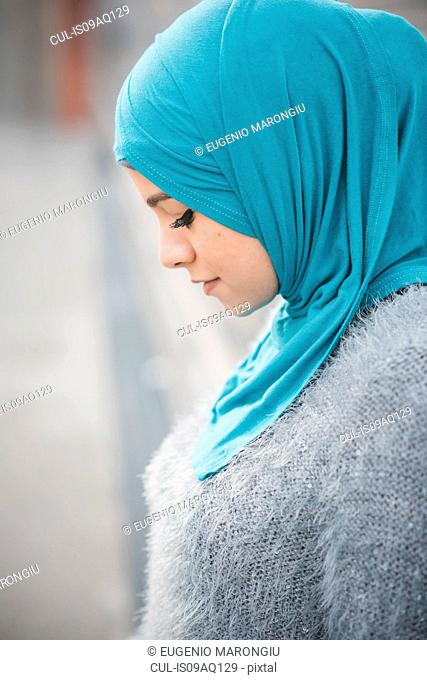 Close up portrait of young woman wearing turquoise hijab on footbridge
