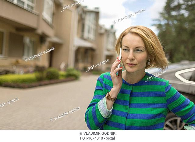 Serious mature woman talking on mobile phone while standing by road in town