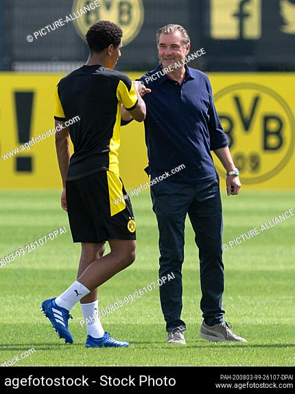 03 August 2020, North Rhine-Westphalia, Dortmund: Newcomer Jude Bellingham (l) and sports director Michael Zorc from Borussia Dortmund welcome each other with a...