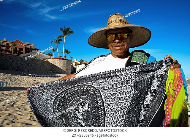 Selling souvenirs to the tourists at the beach in front of The Sheraton Hacienda Del Mar Golf & Spa restort Hotel, in Los Cabos, Mexico, Sea of Cortez