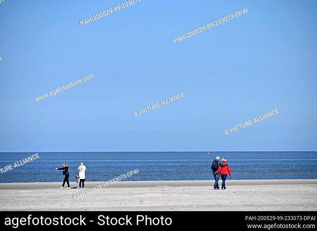 29 May 2020, Schleswig-Holstein, St.Peter-Ording: Visitors walk along the North Sea beach under blue skies. For the North Frisian islands and Halligen of the...