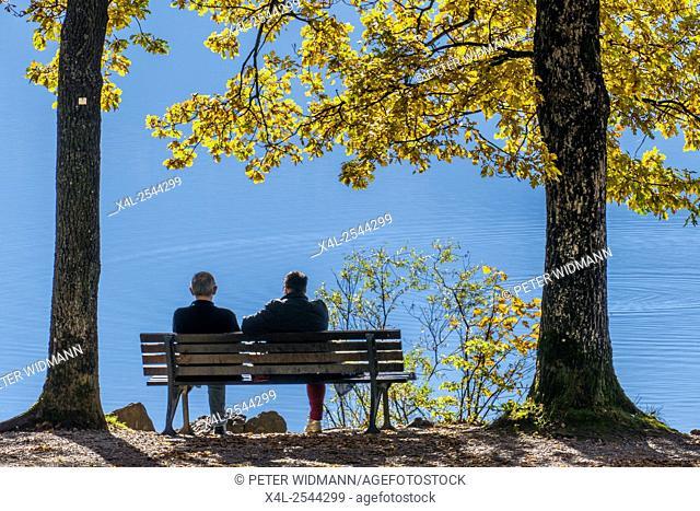 Couple enjoying the last rays of sunshine in the autumn on a bench at a lake, Kochel, Bavaria, Upper Bavaria, Deuschland, Europe