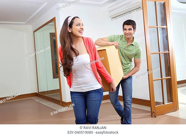 Young man and young woman carrying a carton