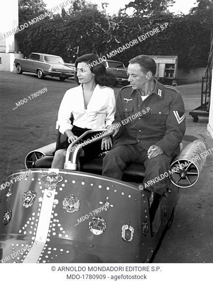 American artist Frank Sinatra as Colonel Joseph Ryan smokes a cigarette sitting onboard a vehicle with Raffaella Carrà as Gabriella; the Italian actress and...