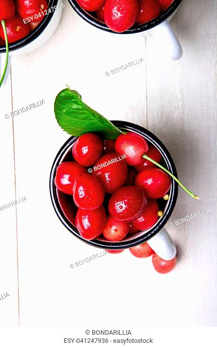 Cherry in enamel cup on white wooden background. Healthy, summer fruit. Cherries. Top view