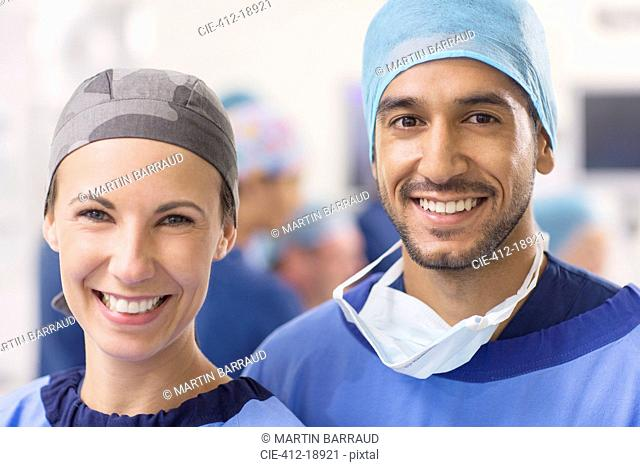 Portrait of smiling doctors wearing surgical caps in operating theater