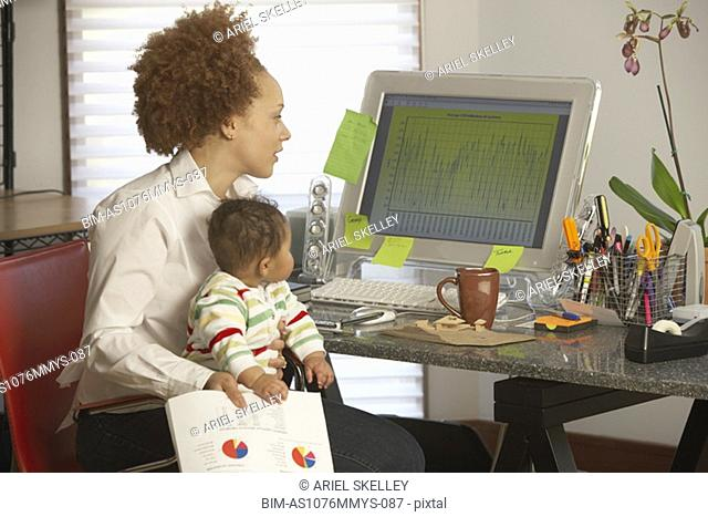 African businesswoman at computer with baby on lap