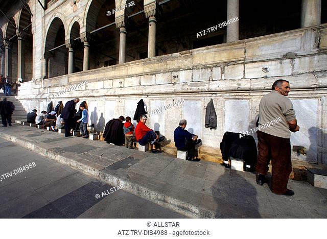 MUSLIMS WASH FEET BEFORE PRAYER OUTSIDE NEW MOSQUE; BAZAAR QUARTER, ISTANBUL, TURKEY; 13/02/2007