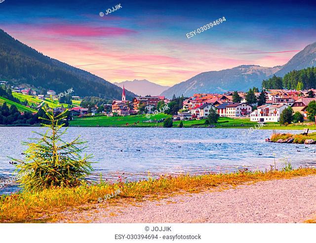 Colorful summer sunrise on San Valentino village from Muta lake (Haidersee). Alps, Italy, Europe