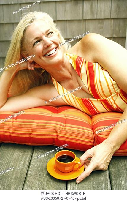 Close-up of a mature woman lying down with a cup of black tea in front of her