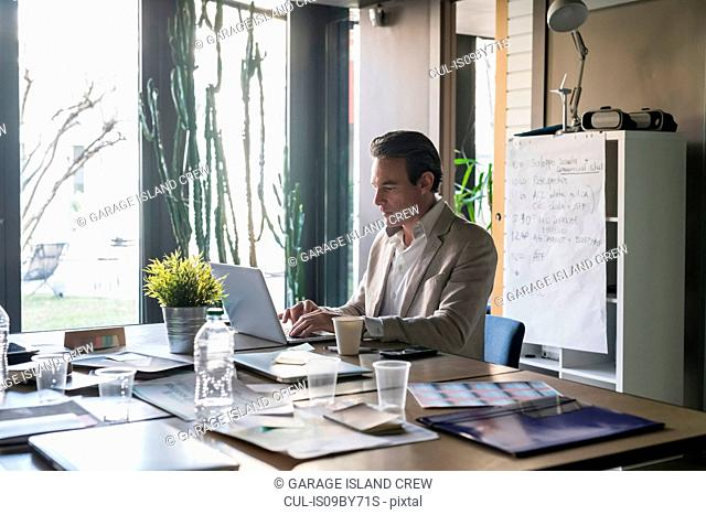 Businessmen using laptop in office