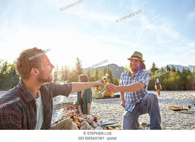 Adult men sitting around campfire making a toast with beer bottles