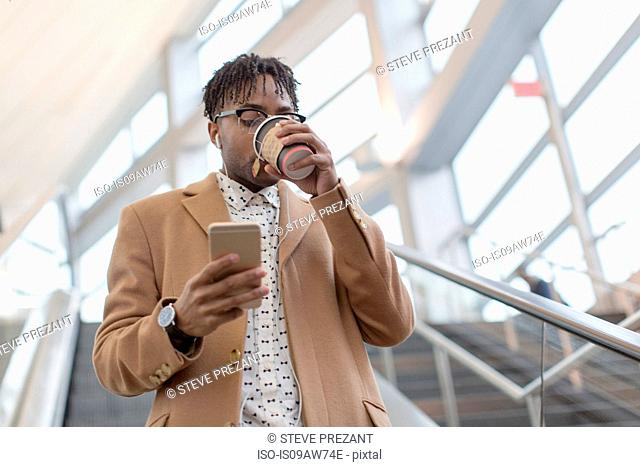 Young businessman moving down train station escalator drinking takeaway coffee