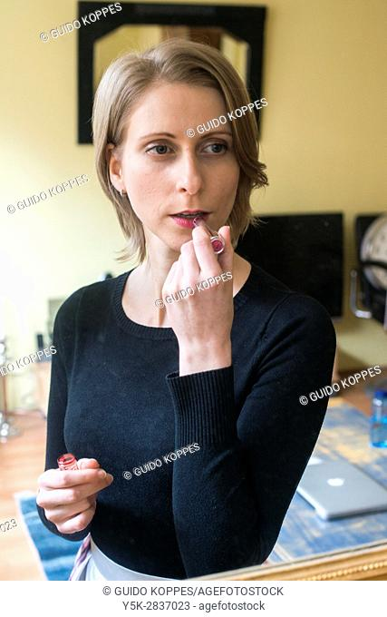 Tilburg, Netherlands. Young adult caucasian woman watching her reflection in a living room mirror while working on her make up