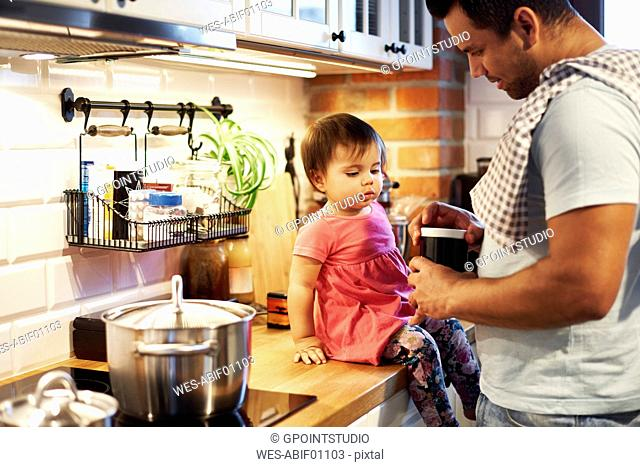 Father and baby girl cooking together in kitchen at home
