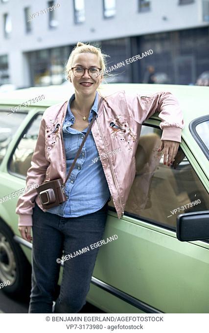 Portrait of woman leaning against vintage car in Berlin, Germany