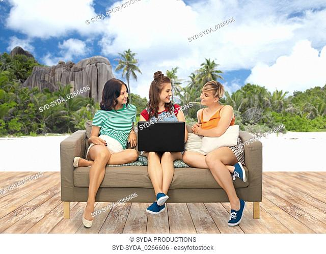 friends with laptop over seychelles island beach