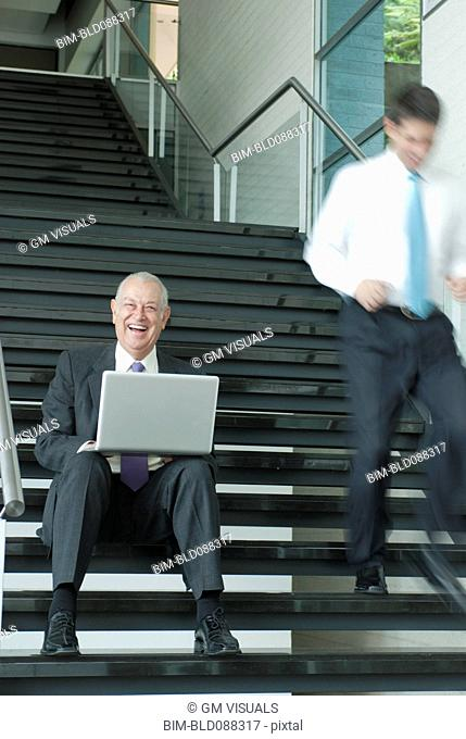 Hispanic businessman using laptop on staircase