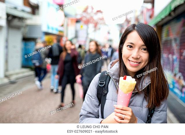 Young Woman enjoy her crape cake at street