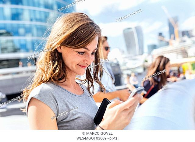 UK, London, smiling woman checking her smartphone
