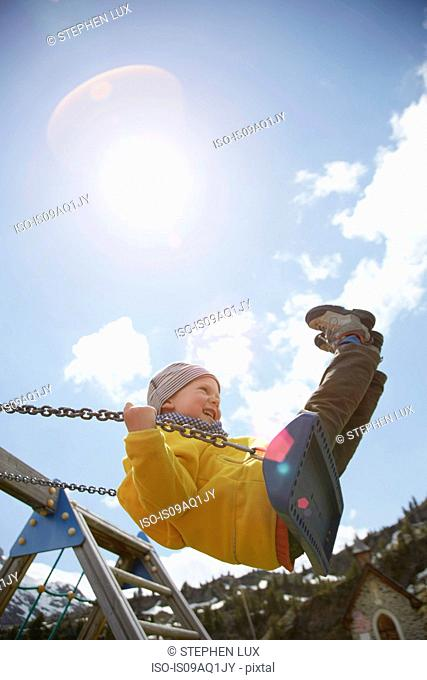 Young boy swinging high on playground swing