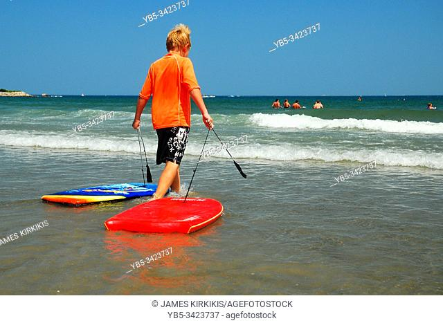 A young boy brings two boogie boards into the ocean