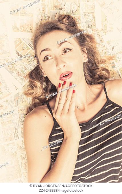 Vintage toned photo of surprised young pin up woman in classic make up and manicure wearing stripy top lying on pop art comic books