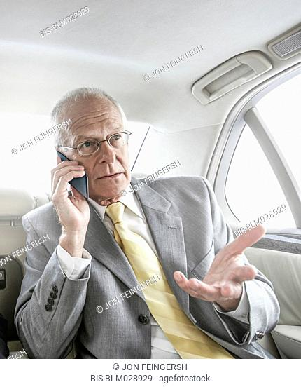 Caucasian businessman talking on cell phone in car