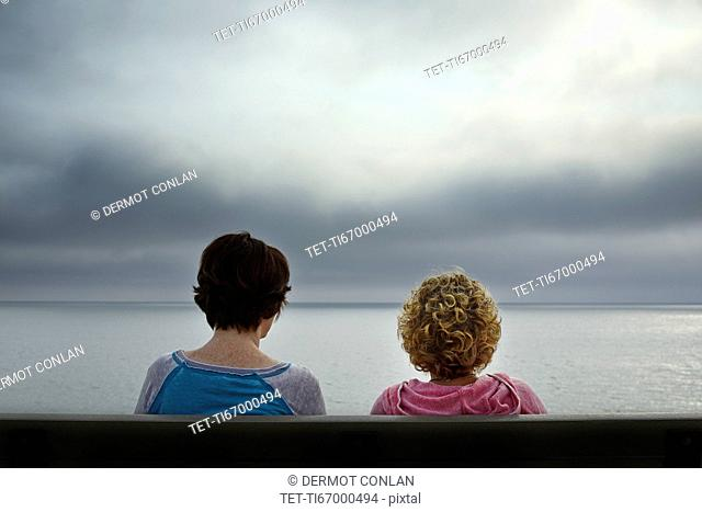 Massachusetts, Cape Cod, Truro, Rear view of two women sitting on bench and looking at sea