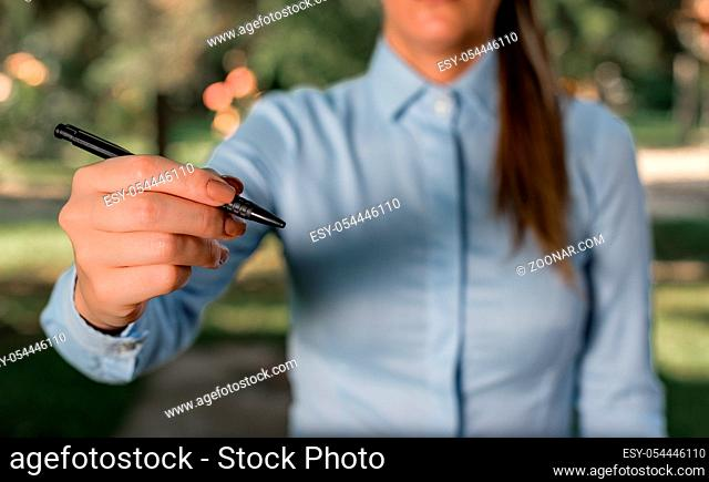 Woman in a blue business shirts pointing with her finger into empty space