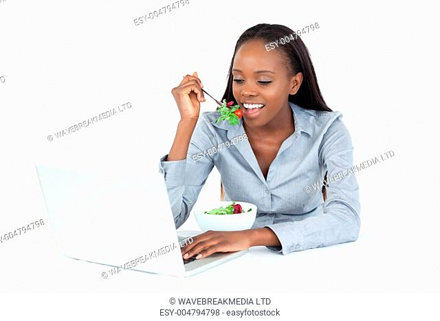 Businesswoman working with a laptop while eating a salad