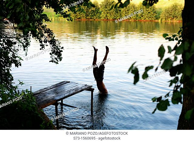 Boy jump from the pier in Lake Avral, Kirillovka, Samara Region, Russian Federation